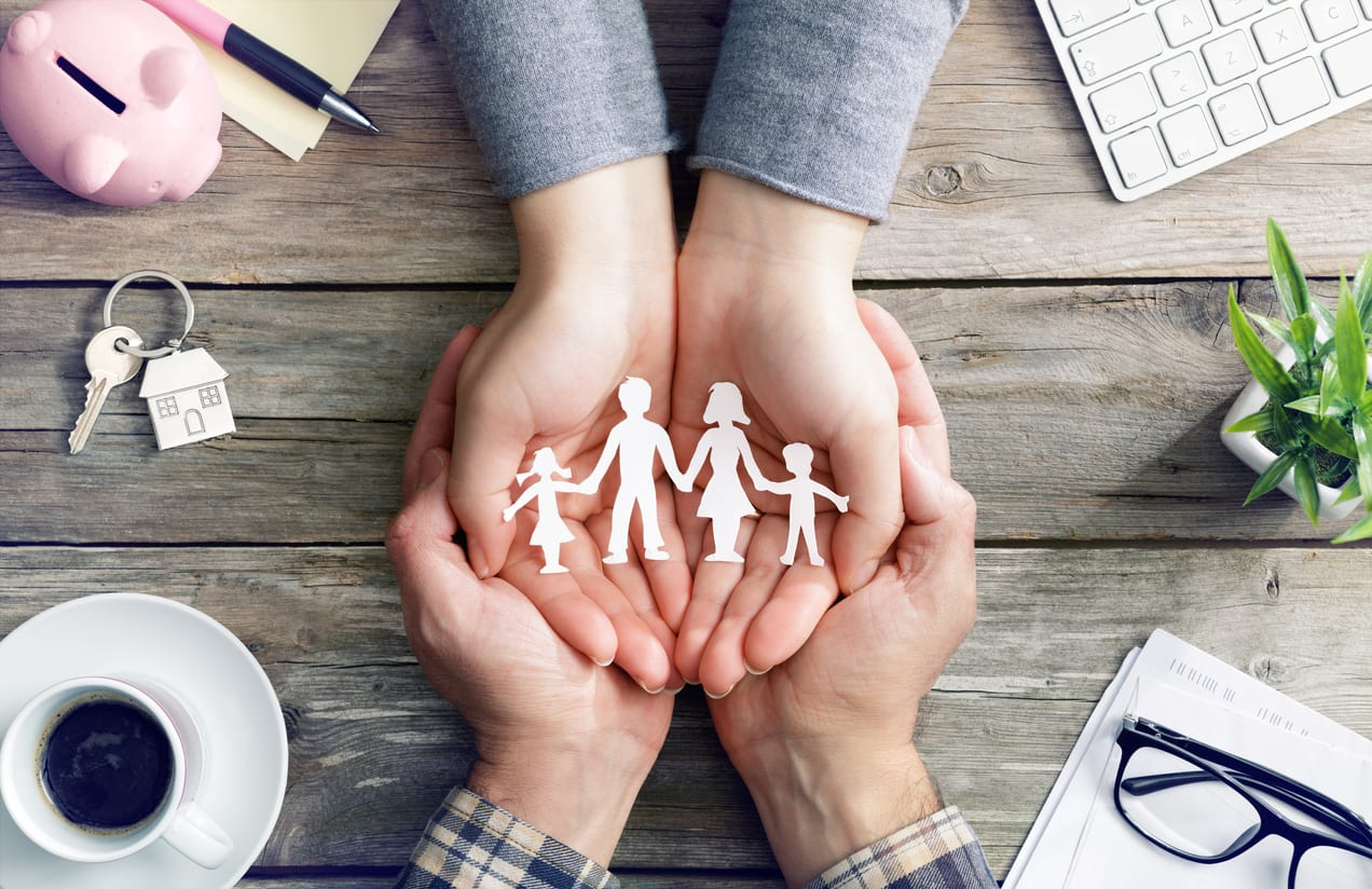 hands in hands protecting paper family